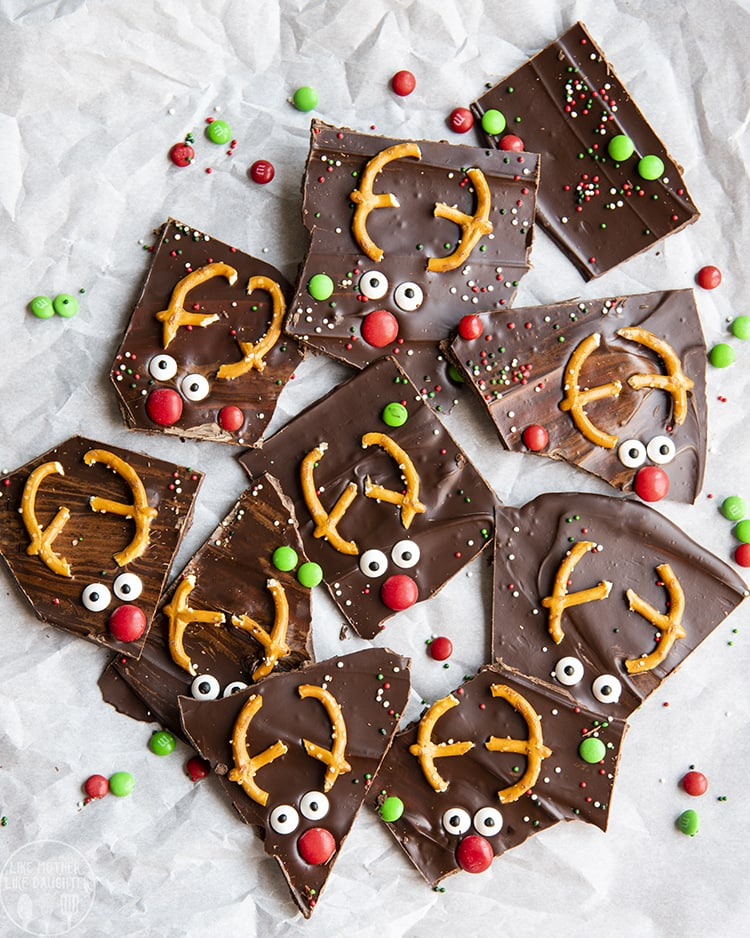 Reindeer Chocolate Bark decorated to look like reindeers with pretzels, candy eyes and m&ms