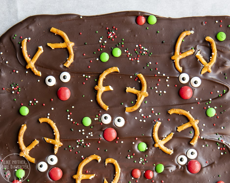 Reindeer Chocolate Bark is topped with m&ms and christmas sprinkles and reindeer faces