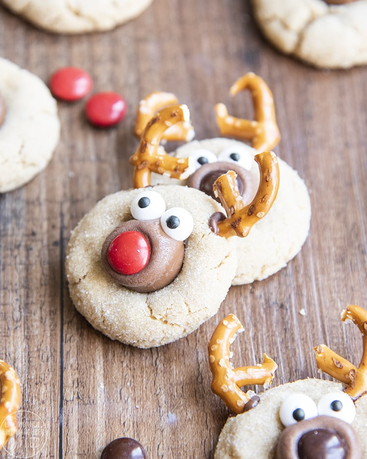 Reindeer Peanut Butter Cookies decorated with pretzels, and candy eyes, and m&m noses to look like reindeer