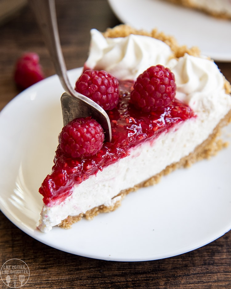 Raspberry Cream Pie with layers of graham cracker crust, cream cheese filling, and raspberry sauce, topped with fresh raspberries