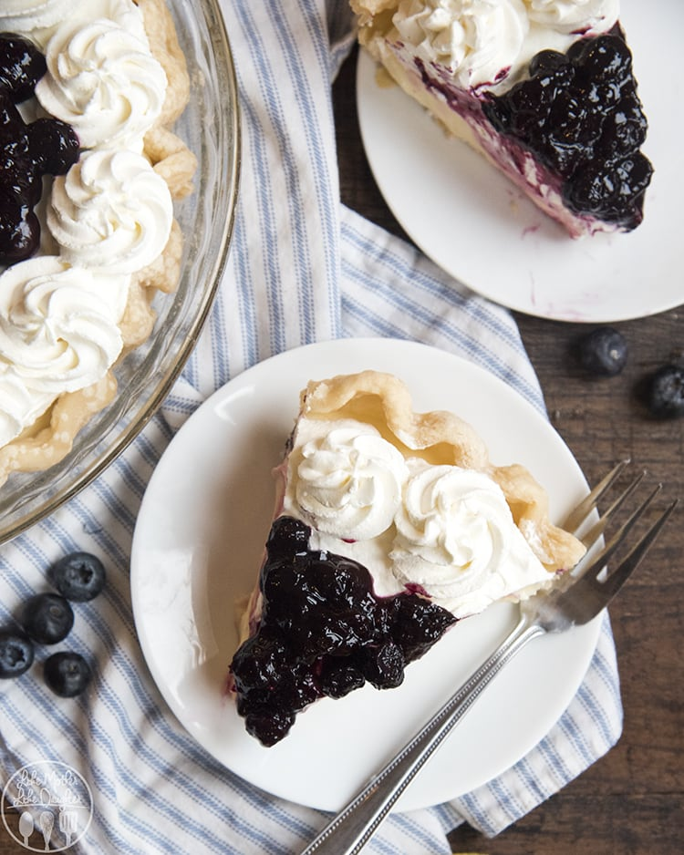 Lemon Sour Cream pie with a creamy lemon custard topped with whipped cream and blueberry sauce