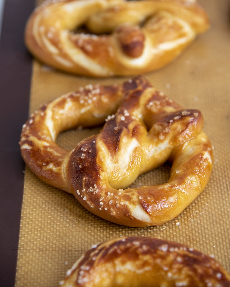 These soft pretzels are the perfect salty, buttery pretzels with a soft and fluffy pretzel middle, and chewy pretzel crust. They're ready in under an hour and are a delicious salty snack.