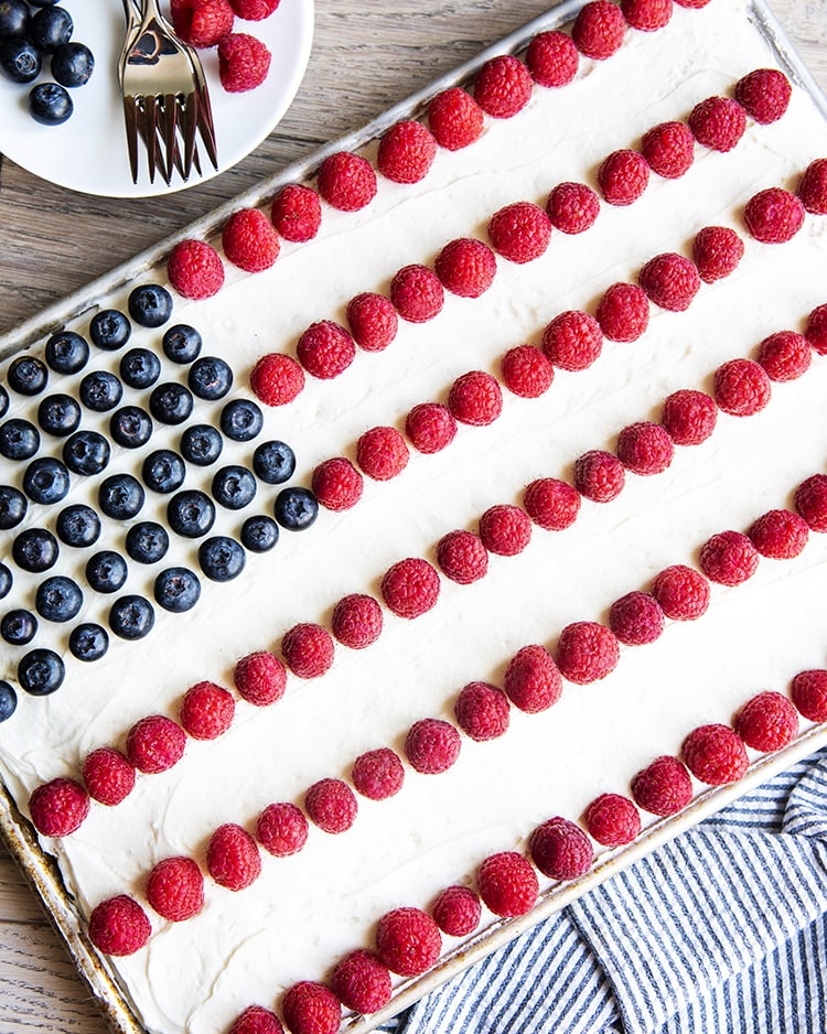 An American flag cake decorated with blueberries and raspberries