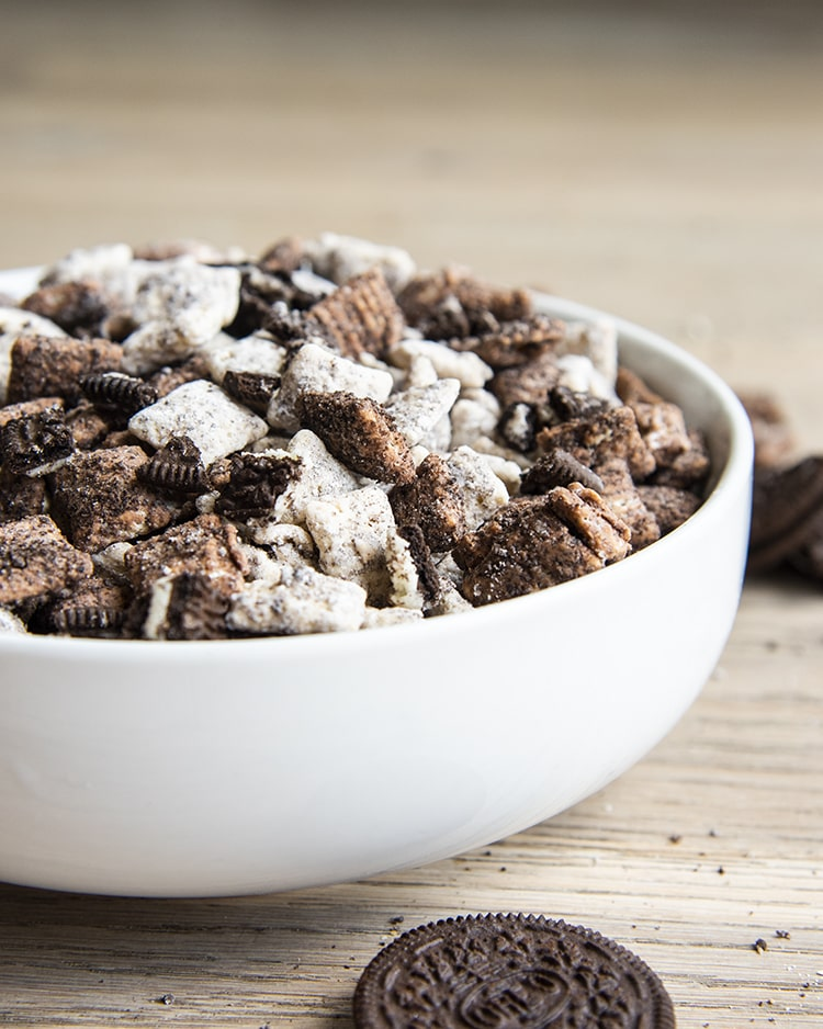 Cookies and cream muddy buddies with chex cereal and oreos in a white bowl.