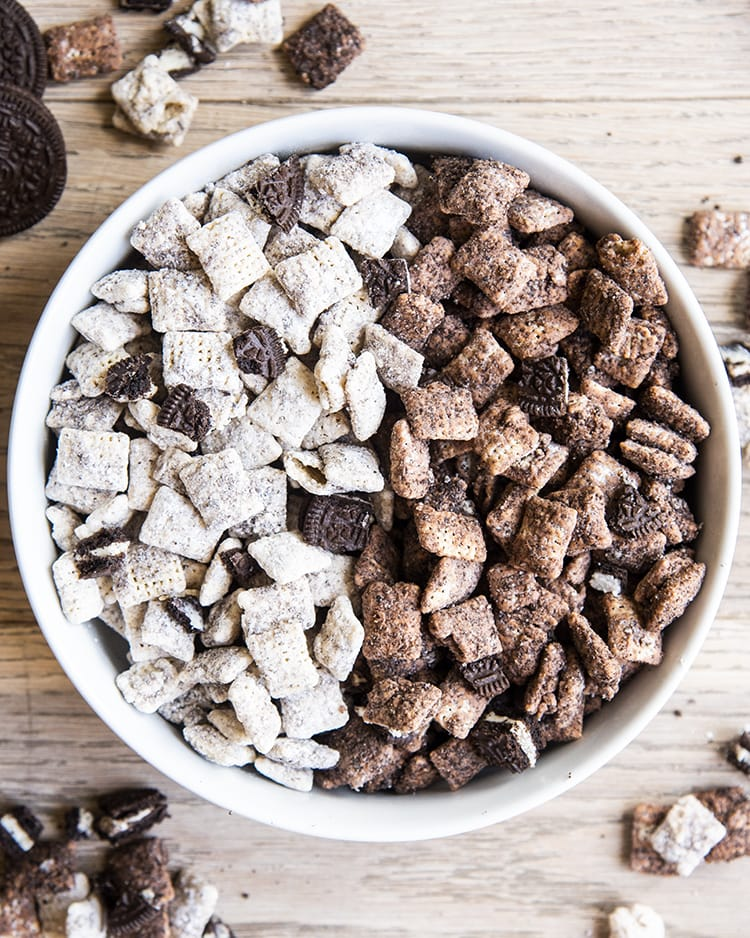 Cookies and cream muddy buddies with half made with white chocolate and half made with chocolate with oreo pieces