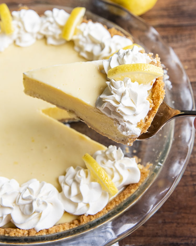 A slice of lemon cream pie being taken out of the pie dish