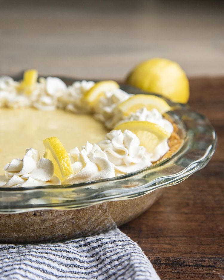 Lemon Cream Pie with Whipped Cream piped around the edges and a quarter of a lemon slice