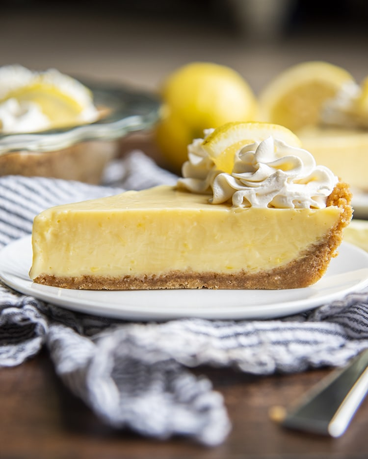 A side view of lemon cream pie with graham cracker crust and whipped cream on top.