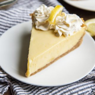 Lemon Cream Pie topped with whipped cream on a white plate