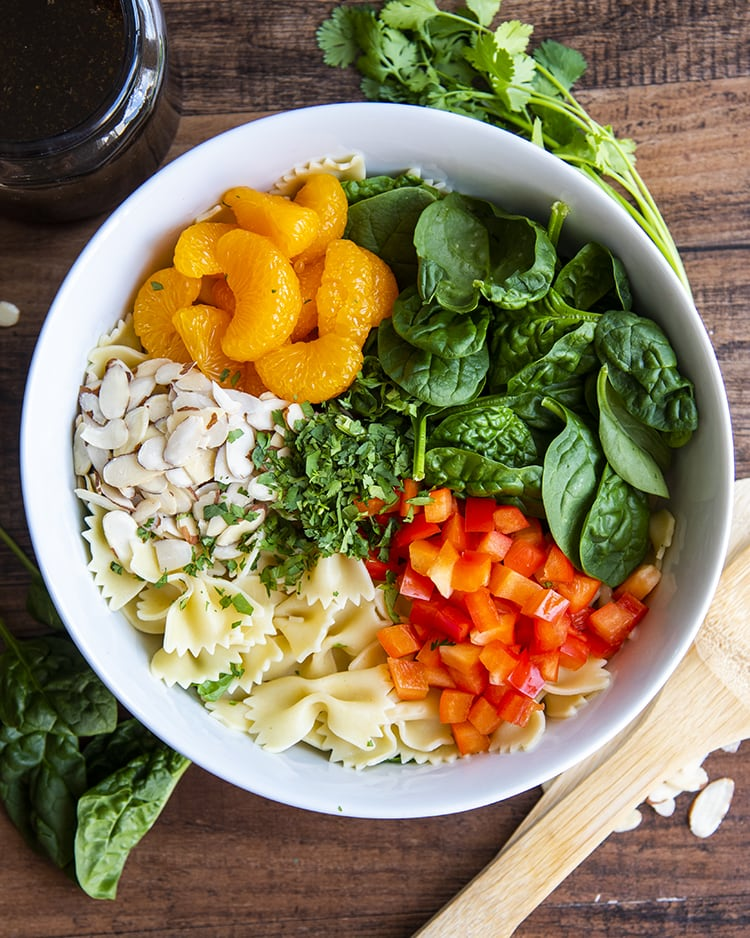Mandarin oranges, spinach, red bell pepper, bow tie noodles, and sliced almonds in a bowl.