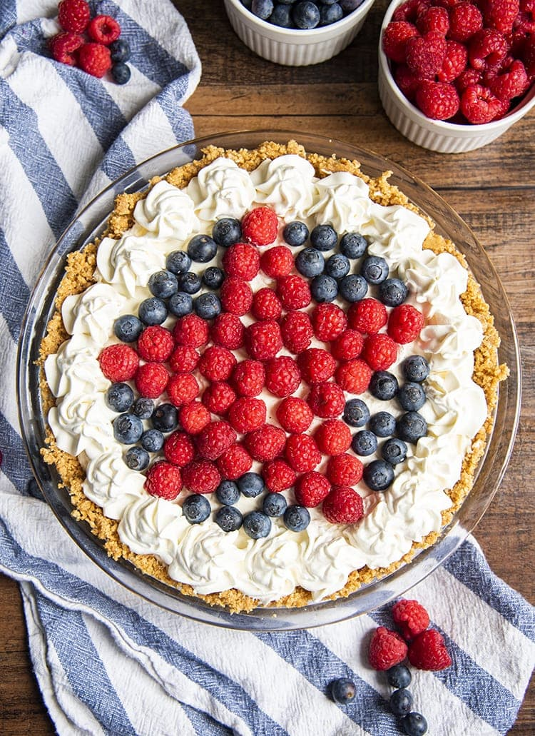 A no bake cheesecake topped with whipped cream on the edges, and a star design with raspberries, and blueberries on the sides
