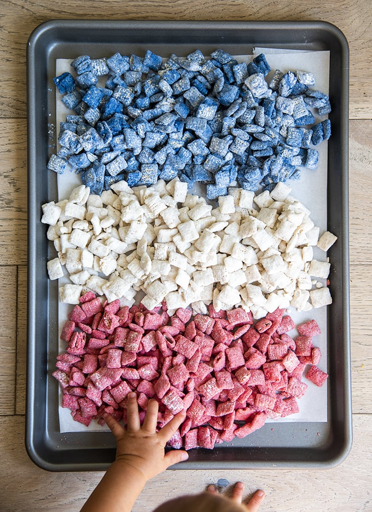Red, white, and blue muddy buddies with m&ms and star sprinkles, separated by color on a cookie sheet with a baby hand reaching to it.