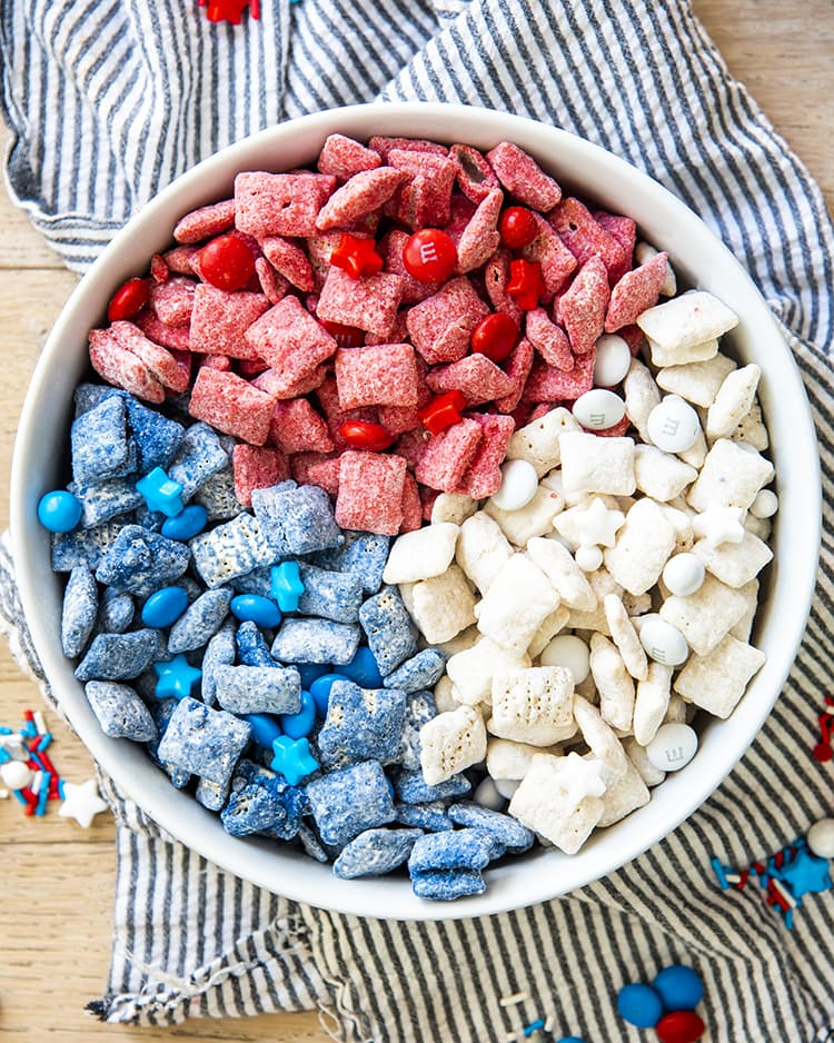 Red, white, and blue muddy buddies with m&ms and star sprinkles, separated by color in a white bowl