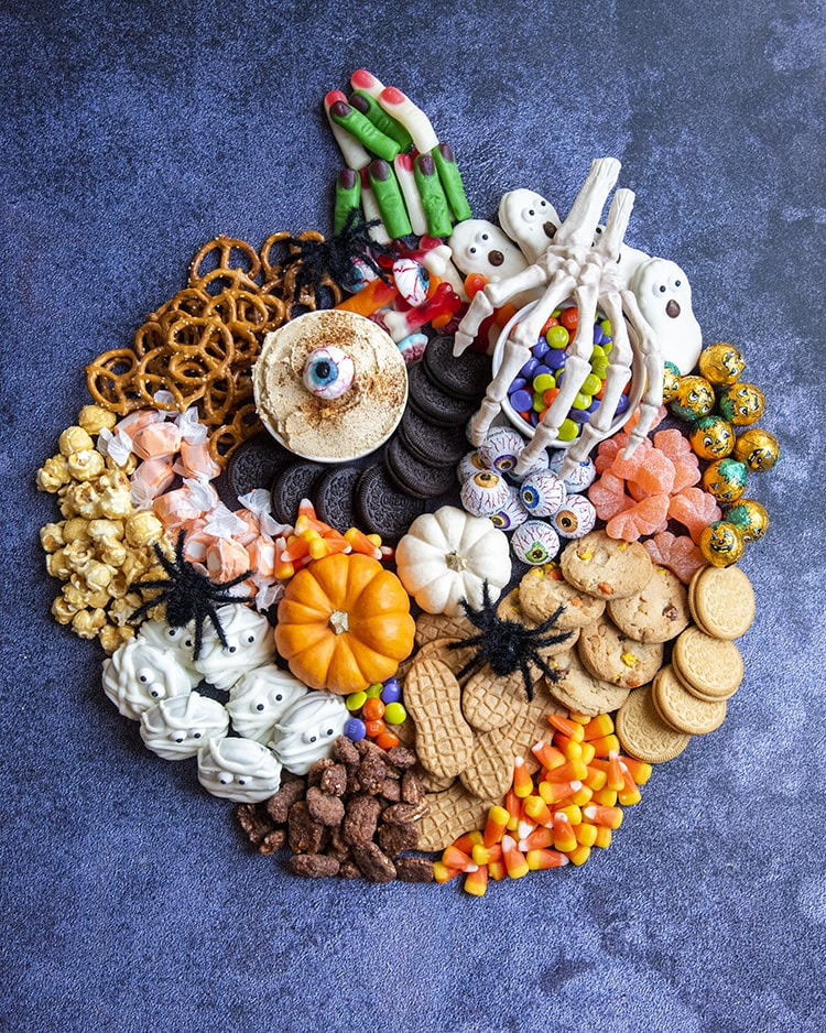 A Charcuterie shaped like a pumpkin and filled with Halloween treats, like candy corn, oreos, pretzels, candy and more.