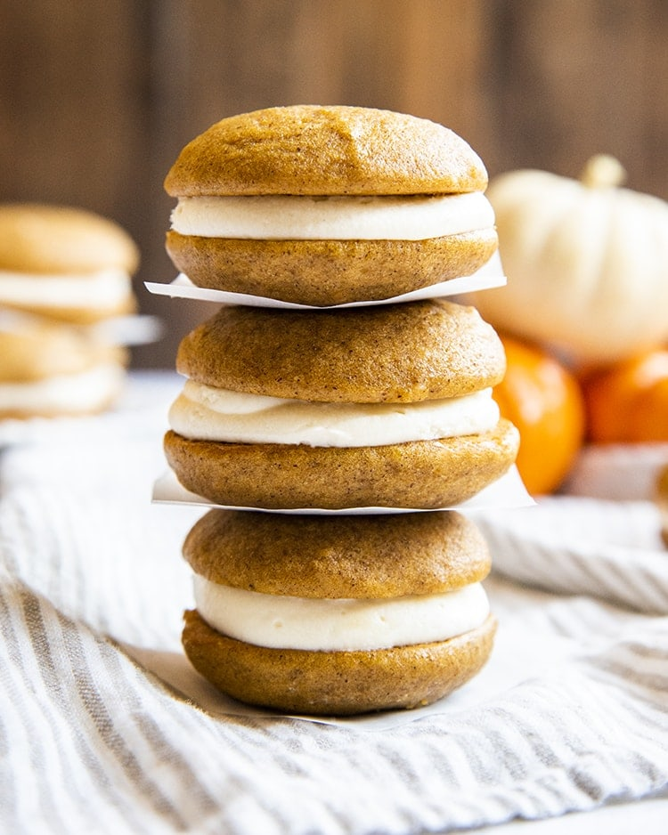 Three pumpkin whoopie pies filled with cream cheese frosting stacked on top of one another with parchment paper in between.