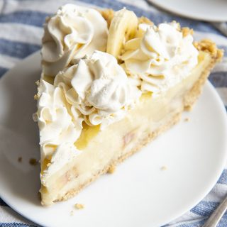 A slice of banana cream pie made from scratch. The slice is topped with whipped cream dollops and has a graham cracker crust.