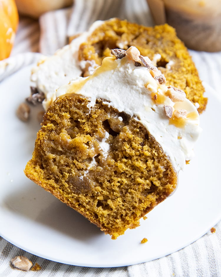 A pumpkin cupcake cut in half showing the moist middle of the pumpkin, topped with frosting.