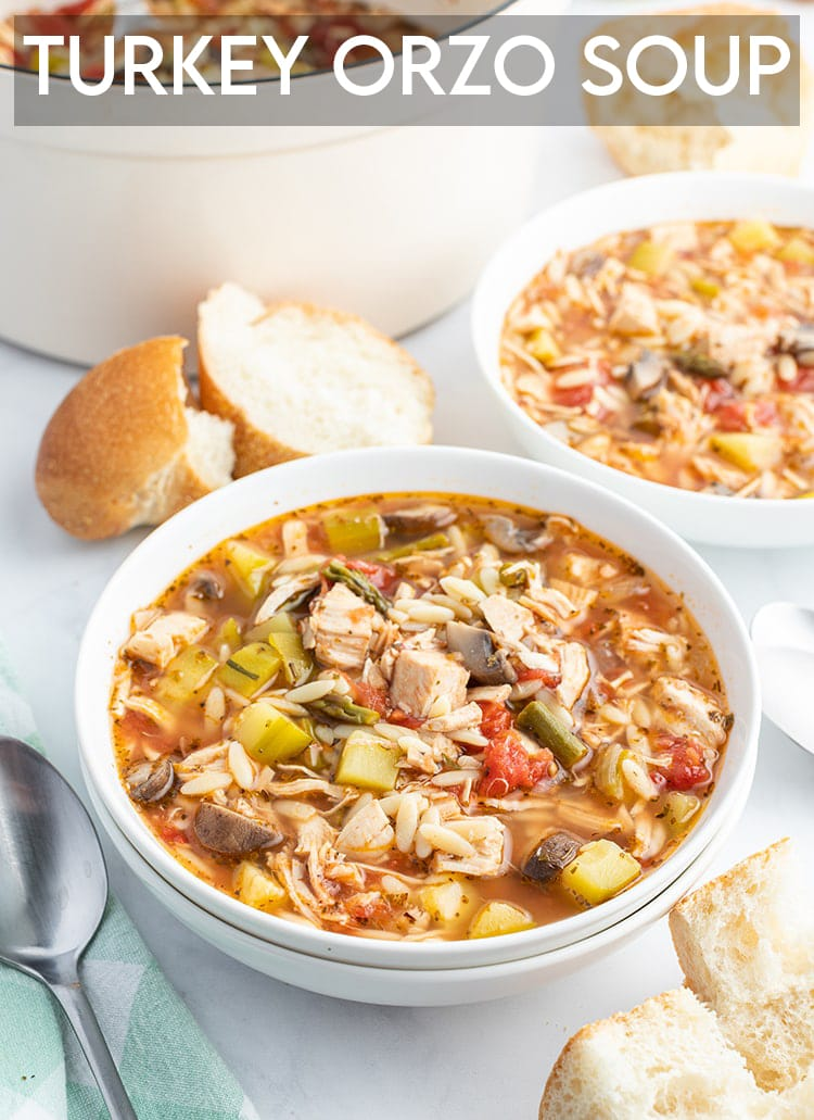 A bowl of turkey and orzo soup with french bread on the side with a text overlay for pinterest.