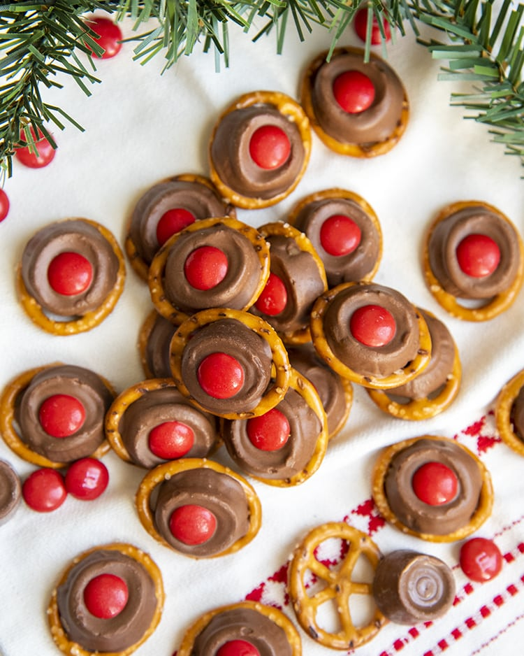 A pile of rolo pretzel treats on a white and red cloth.