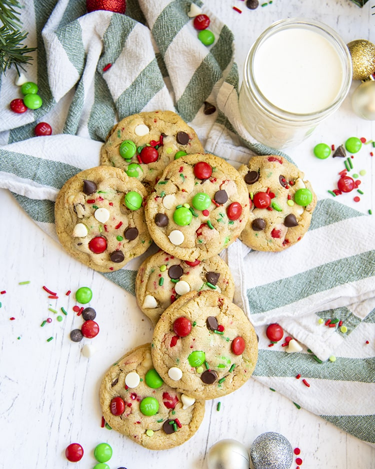 A pile of Christmas cookies on a green and white striped cloth.