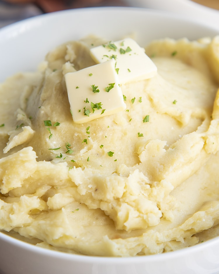 A big bowl of slow cooker mashed potatoes topped with butter and sprinkled with parsley.