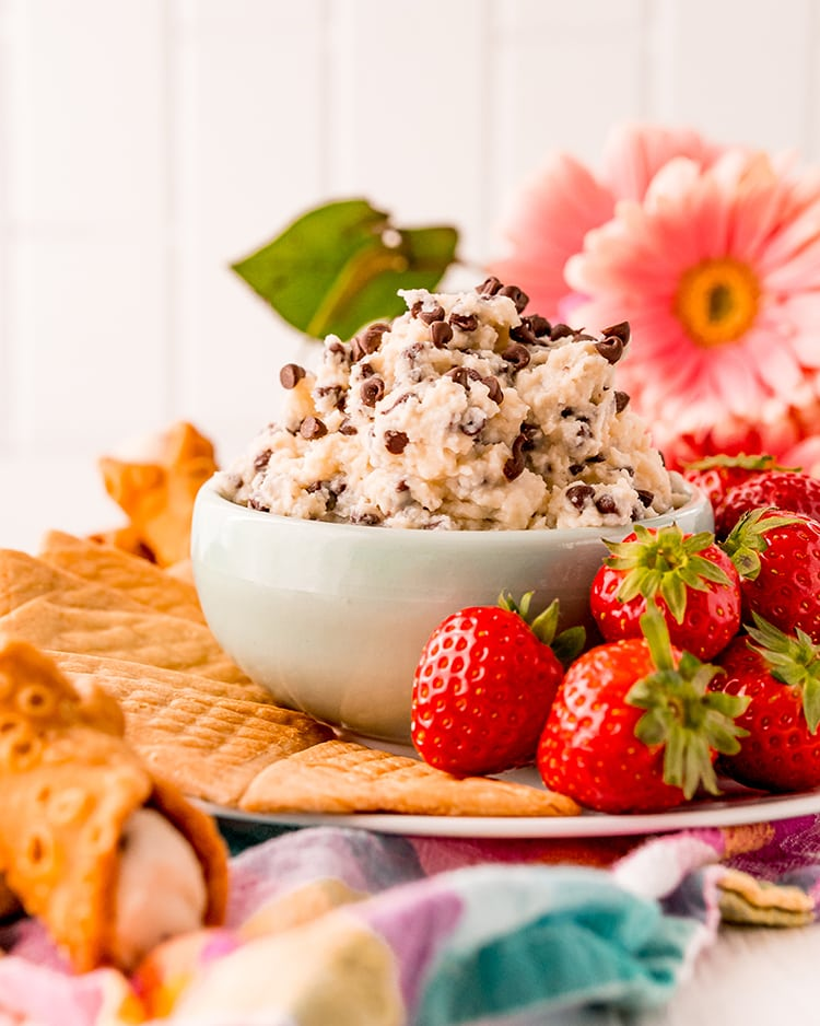 A small bowl of cannoli dip sprinkled with mini chocolate chips. The bowl is a on a plate with crepe cookies, and strawberries. There are pink flowers behind the bowl.