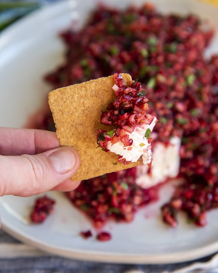 Cranberry salsa and cream cheese on a square wheat thin cracker in front of a plate of cranberry salsa over a block of cream cheese.