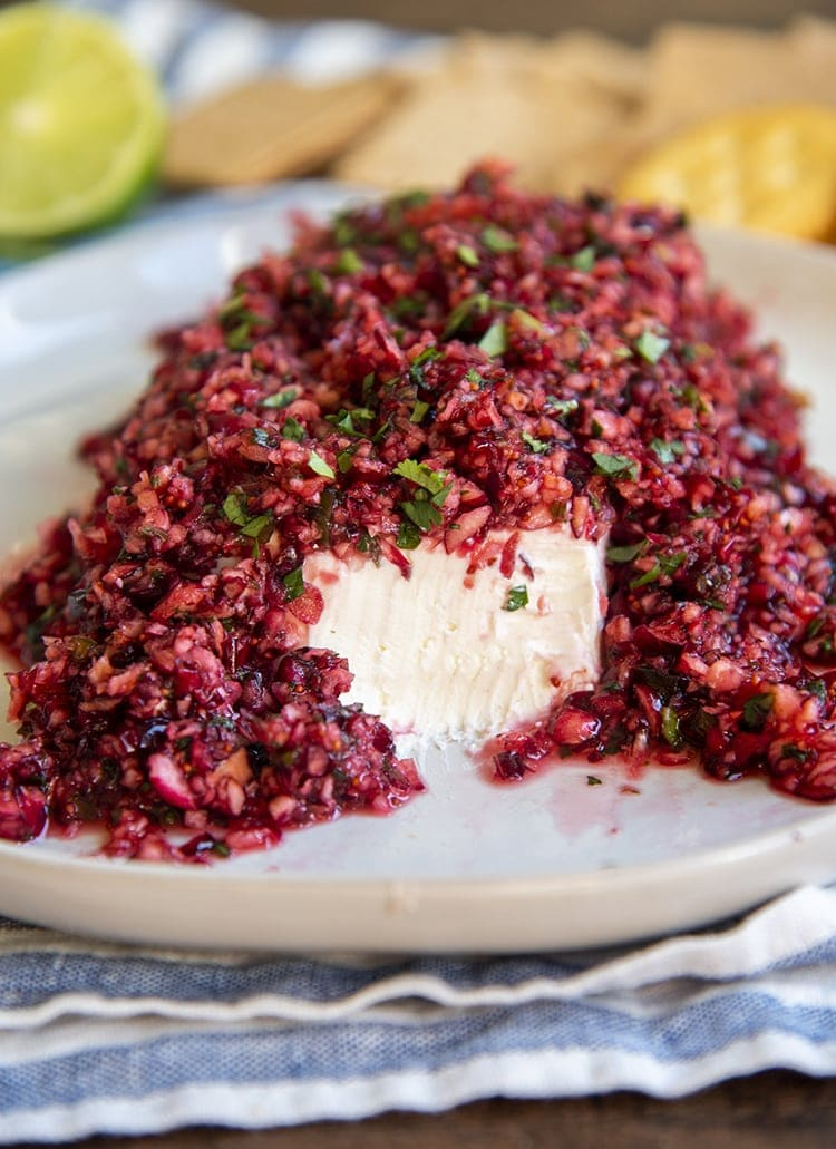 A slab of cream cheese topped with cranberry salsa, full of chopped up cranberries and cilantro. The front of the cream cheese is showing
