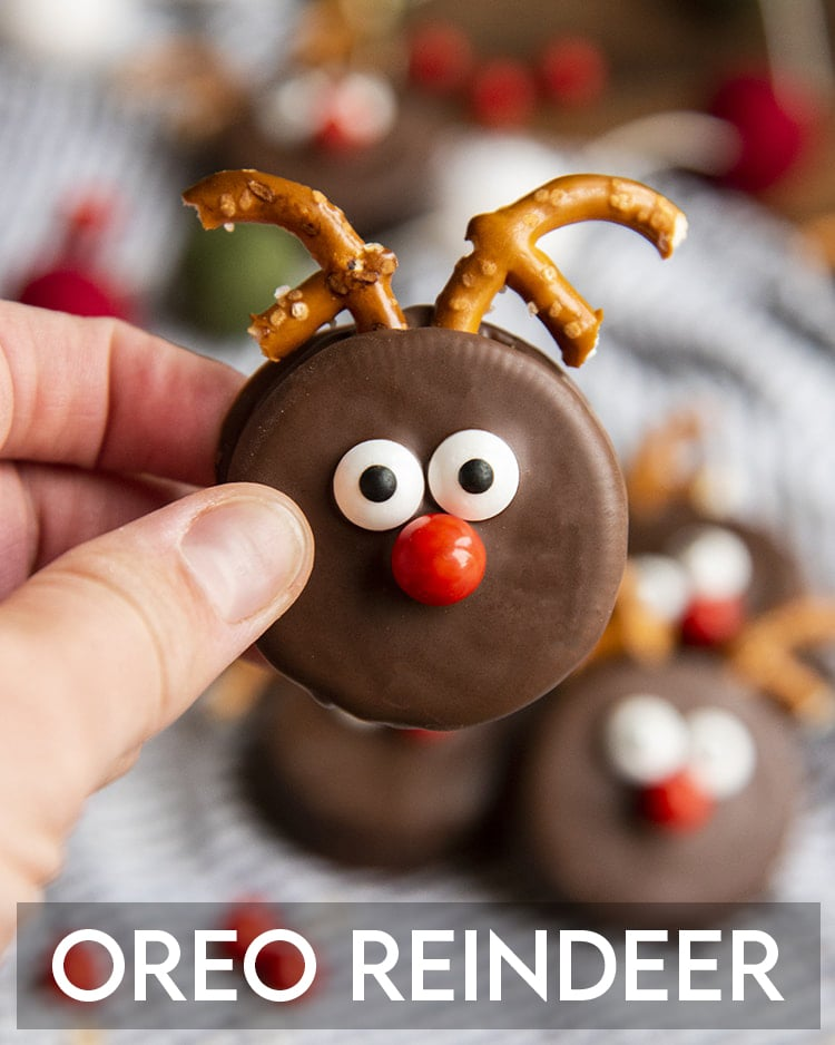 An Oreo dipped in chocolate and decorated to look like a reindeer with pretzel pieces for antlers, candy eye balls and a red sixlet nose. It's being held up by a hand with a text overlay at the bottom for pinterest.