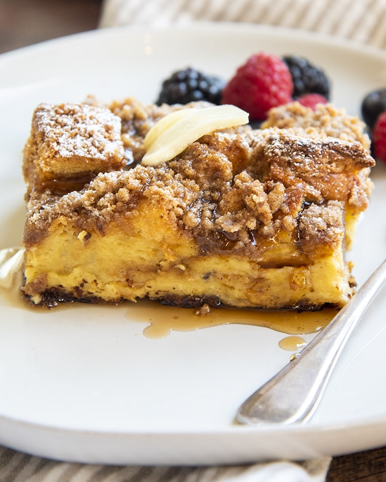 A piece of overnight french toast casserole topped with berries and syrup.