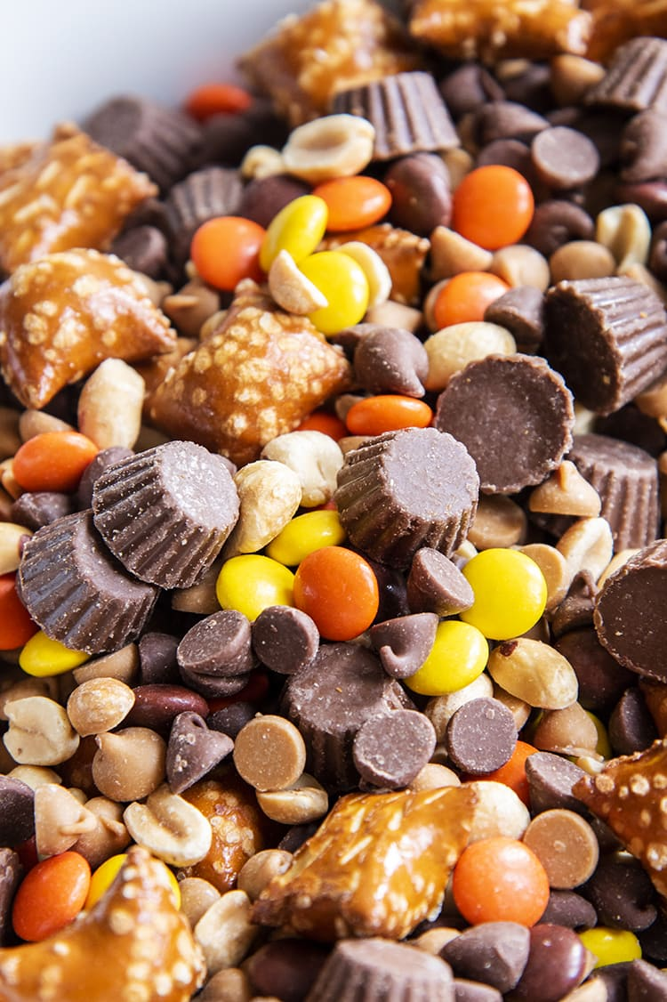 A close up of a chocolate peanut butter trail mix full of mini peanut butter cups, peanut butter filled pretzels, reeses pieces, peanuts, chocolate chips, and peanut butter chips.