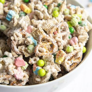 A close up of a a bowl of a lucky charms snack mix, with cereal, marshmallows, and green chocolate candies covered in melted white chocolate.