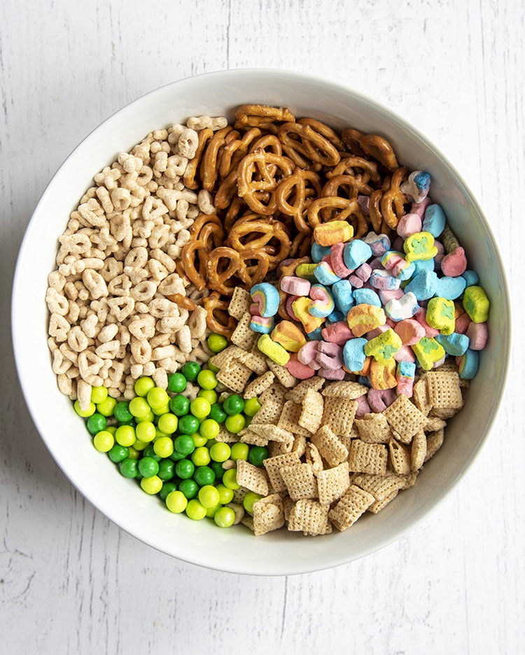 A bowl of 5 ingredients separated, mini pretzels, lucky charms marshmallows, chex cereal, green sixlets, and lucky charms cereal without the marshmallows.