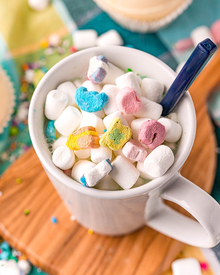 A white mug full of hot cocoa and topped with mini marshmallows and lucky charms marshmallows.