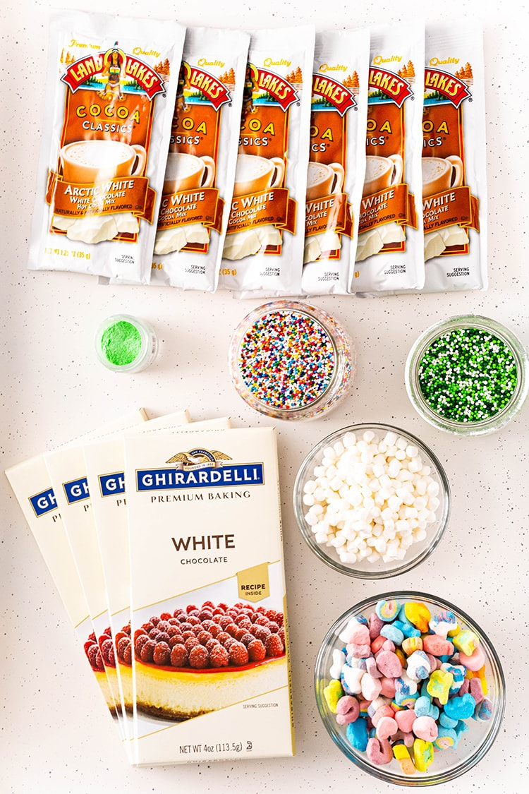 The ingredients needed to make white hot  chocolate bombs. There are packs of white chocolate cocoa mix, white chocolate baking chocolate bar, bowls or sprinkes, a bowl of mini marshmallows, and a bowl of lucky charms marshmallows.
