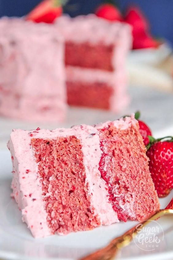A slice of a double layered strawberry cake on a plate, with a pink strawberry frosting.