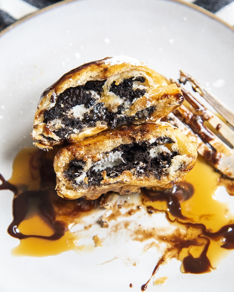 An air fried Oreo cut in half on a plate in a pile of caramel sauce and chocolate syrup.