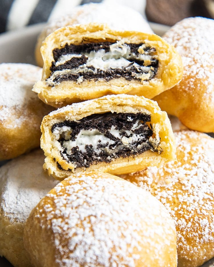 Air Fried Oreos in a bowl covered in powdered sugar, and there is one on top that is cut in half showing the Oreo in the middle.