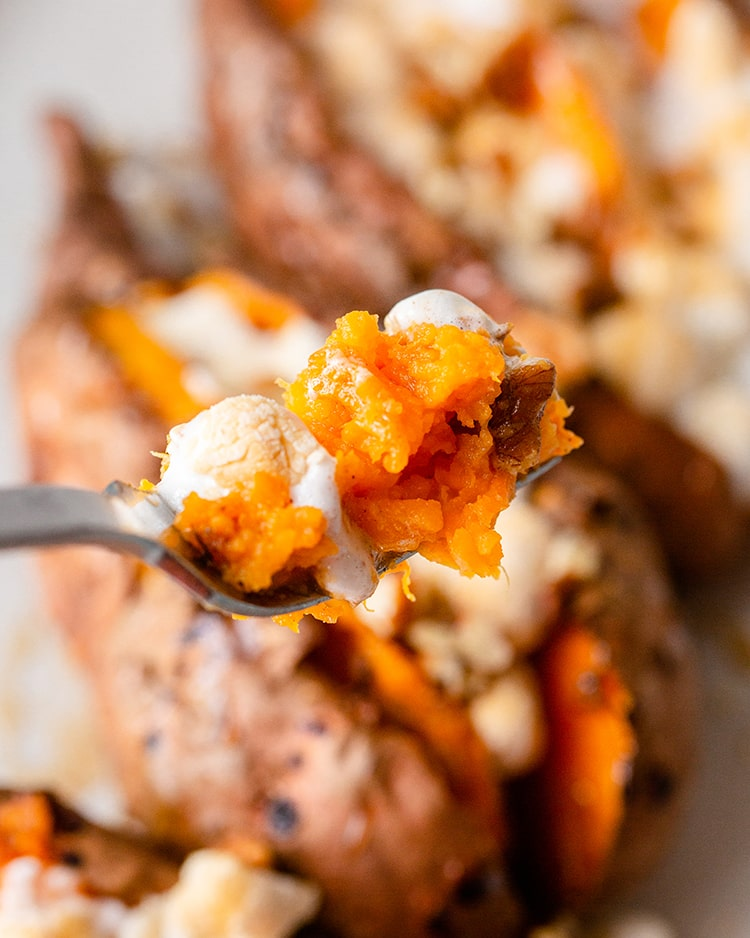 A bite of sweet potato and toasted marshmallow on a fork.