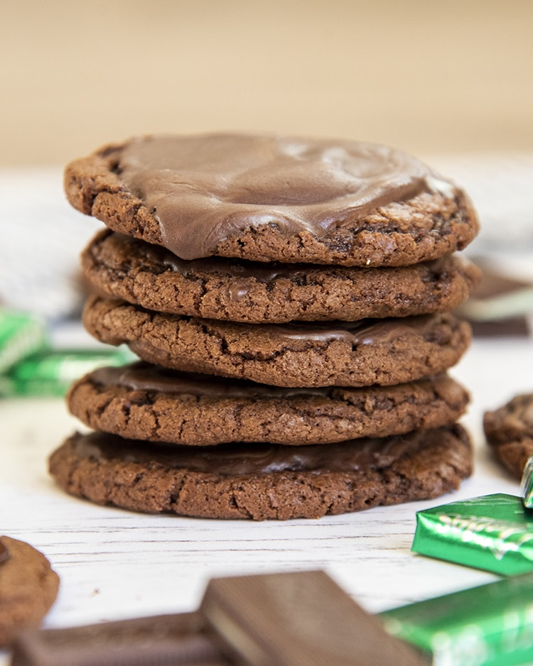 A stack of chocolate cookies, 5 cookies high. The top cookie looks like it has chocolate ganache on it.
