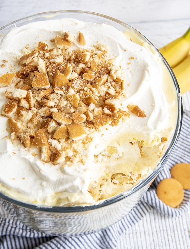 A banana pudding trifle with a serving scooped out of it, so you can see the yellow pudding underneath the top whipped cream layer.