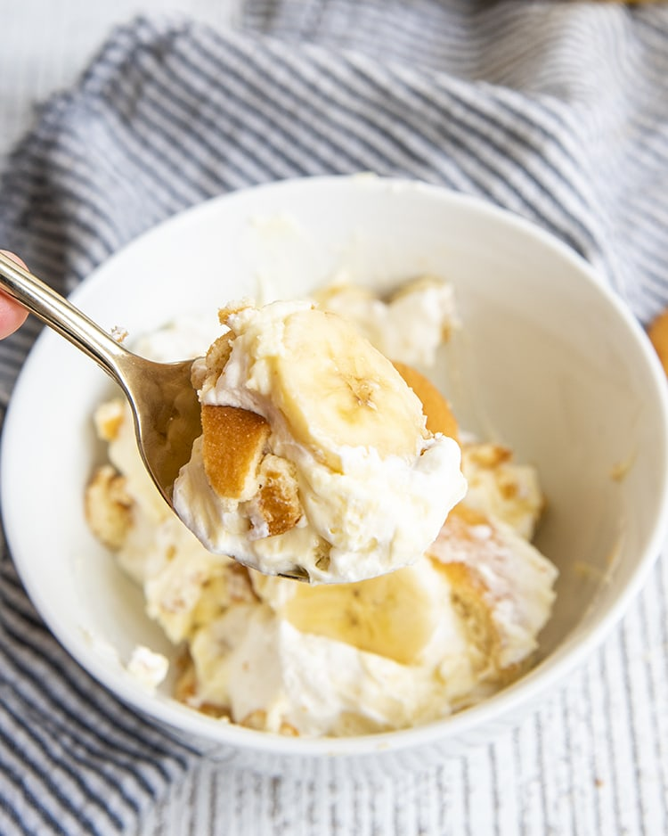 A bowl of banana pudding, with a spoonful of it being held above it.