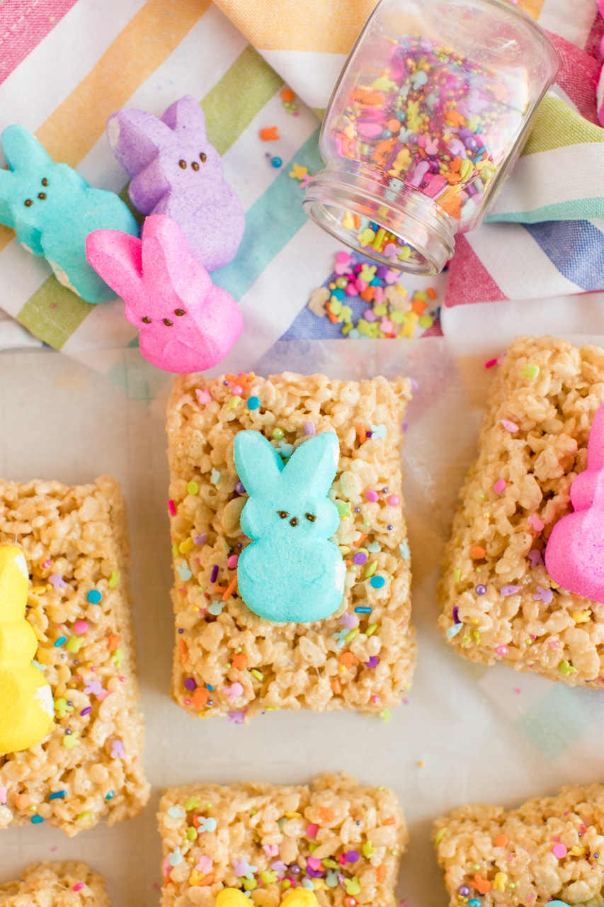 Rice Krispie treats decorated with funfetti colored sprinkles and topped with a Peeps bunny. There are more peeps laying along side them.