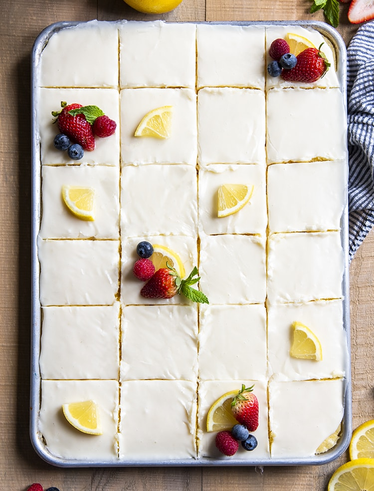 A baking pan full of cake shot from the top showing the icing, and cake cut into slices. Some of the slices have a quarter of a lemon slice and some berries.
