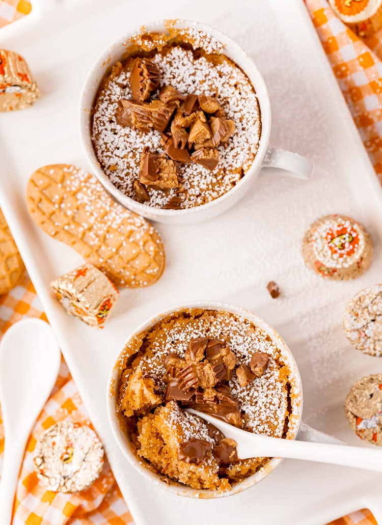 Two peanut butter nutter butter mug cakes on a white tray. They are topped with chopped peanut butter cups.
