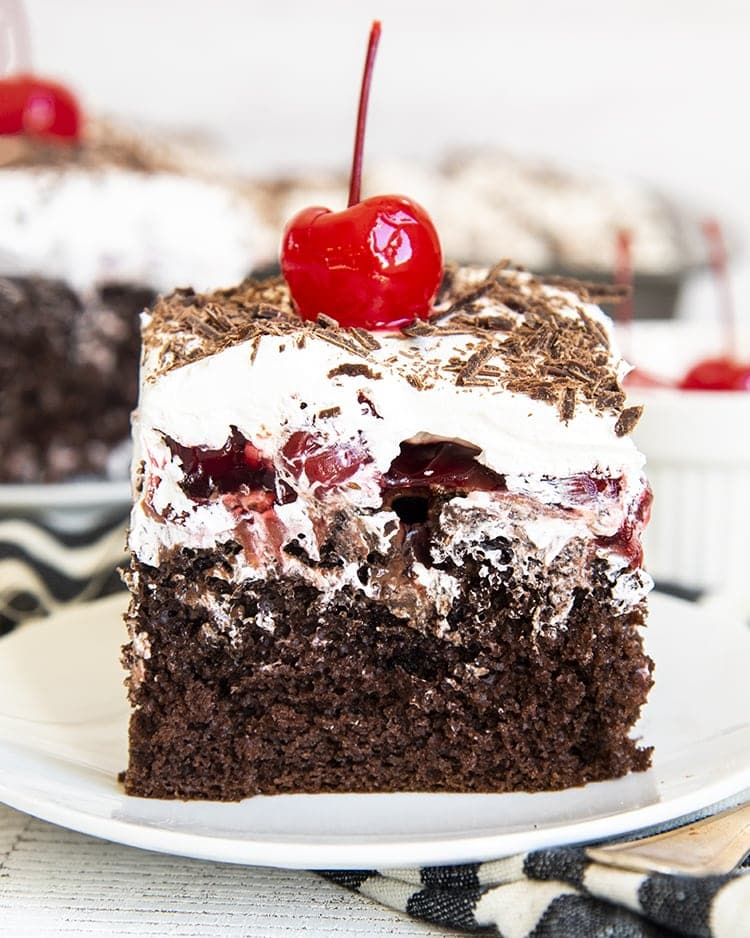 A square piece of chocolate cake on a small pan topped with cherries, and whipped cream with chocolate shavings over the top. There is a maraschino cherry on top of the whipped cream.