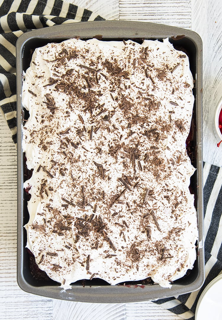 An overhead shot of a 9x13 pan of cake, you can see the whipped cream topped with chocolate shavings spread over the top.