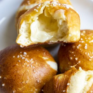 A plate with ball shaped soft pretzels, one is opened up, showing white melted cheese in the middle.