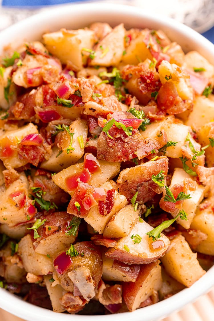 A close up of German potato salad with big pieces of red potatoes, bacon, red onion, and sprinkled with chopped parsley.