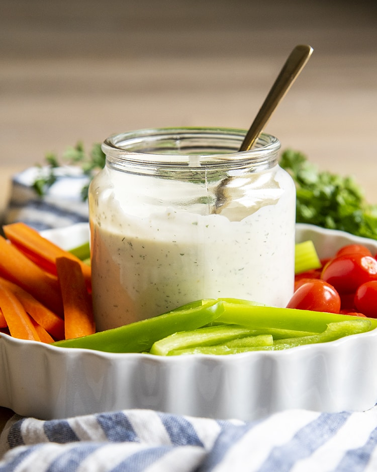 A clear jar full of homemade ranch dressing, about 3/4 with a spoon also in the jar. It is on a tray with sliced vegetables.